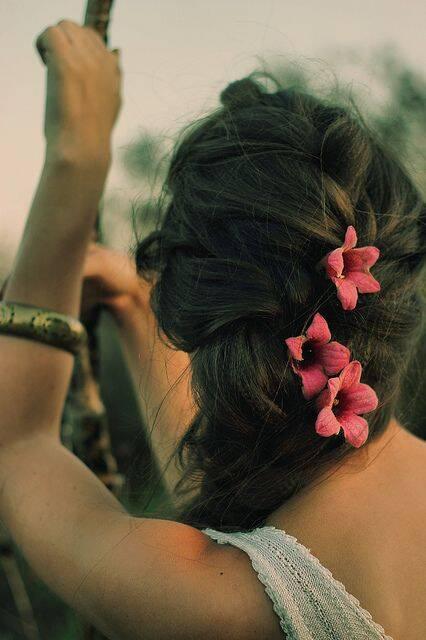 A trança despojada ganhou flores para deixar o look romântico (Foto: Pinterest)