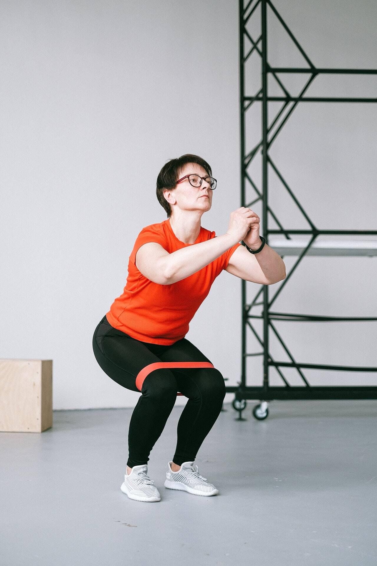 Comece a se abaixar em uma posição de agachamento ou até se sentir confortável, mantendo as costas retas, o peso sobre os calcanhares e os joelhos atrás ou alinhados com os dedos dos pés. Mantenha as pernas estendidas durante todo o movimento, certificando-se de que os joelhos não dobrem. Em seguida, volte à posição inicial. Esta é uma repetição; Faça 3 séries de 10-15 repetições. (Foto: Pexels)