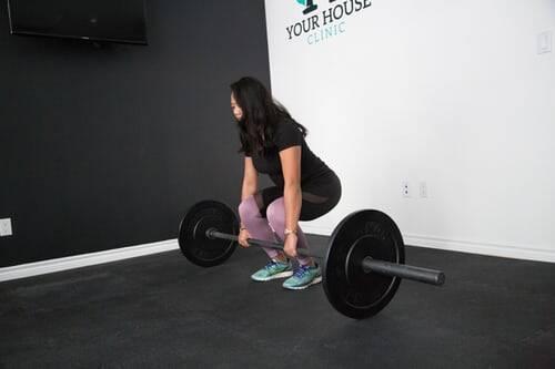 Fique em pé com os pés ligeiramente mais largos do que a largura do quadril, com uma faixa de resistência logo acima dos joelhos. (Foto: Pexels)